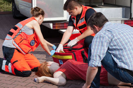 rescuer: Emergency service helping unconscious woman on the street