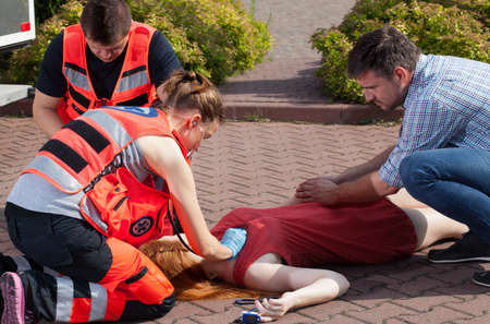 rescuer: Couple of paramedics examining woman on the street