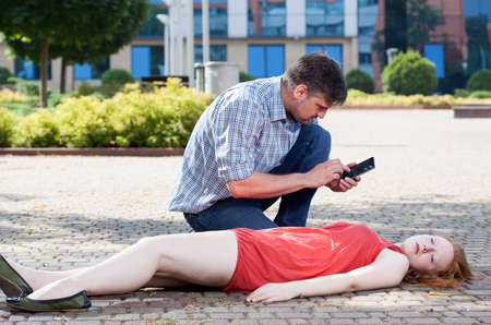 unconscious: Man calling emergency service on the street Stock Photo