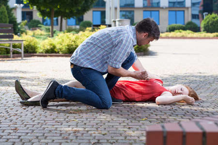 Man trying to help unconscious woman on the street Imagens