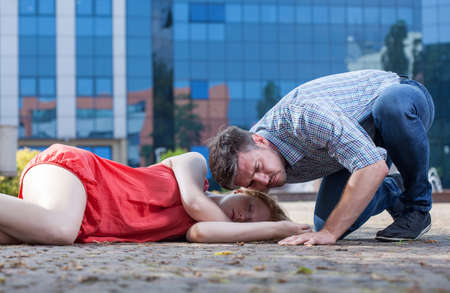 first help: Man checking if womans breathing on the street Stock Photo