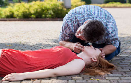 View of man checking if woman's conscious Stock Photo