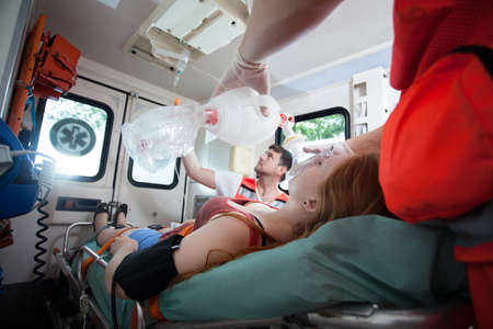 paciente en camilla: Mujer herida necesita oxígeno en ambulancia, horizontal