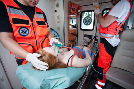 Unconscious woman and working paramedics in ambulance
