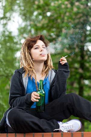 jovenes tomando alcohol: Teenage chica bebiendo cerveza y fumar cigarrillos, vertical
