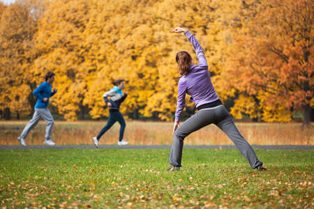 Athletic woman stretching in autumn glade after jogging photo