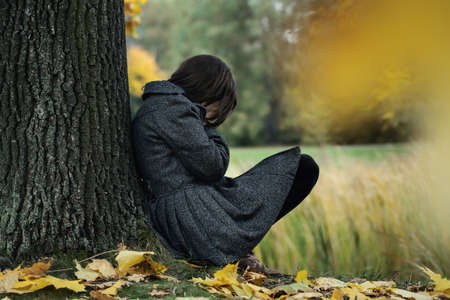 beautiful crying woman: Wonan sitting on the ground and crying in the park Stock Photo