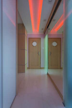 view an elegant wardrobe: Modern corridor with red neon lighting, vertical