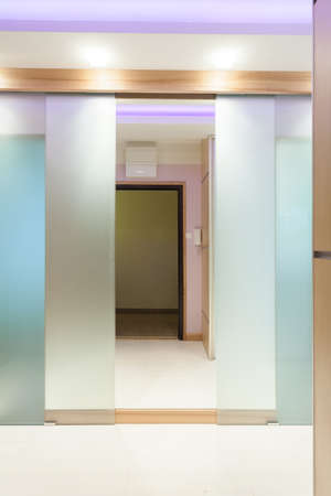 glass doors: Open illuminated door in modern apartment, vertical