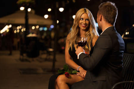 Loving couple drinking wine during proposal at night photo