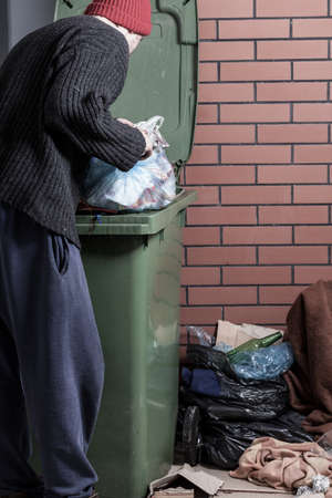 lost city: Homeless man looking for something in the trash Stock Photo