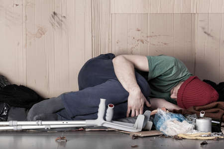 unhealthy living: Homeless disabled man on the street, horizontal Stock Photo