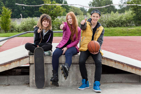boy skater: Young friends pointing their thumbs up at a skate park