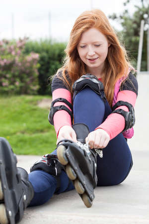 blading: Redhead girl sitting on the ground and putting on rollerskates