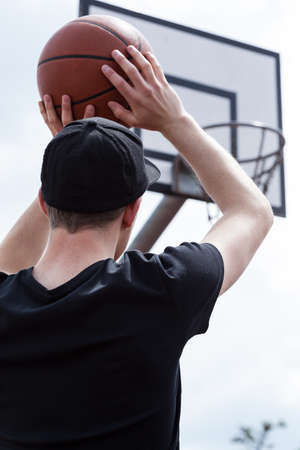 Young man throwing a basketball into the hoop photo