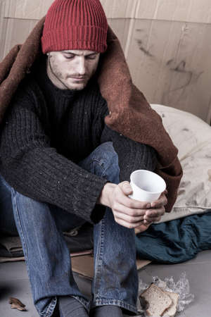 Cold and sad homeless man begs for money Stock Photo