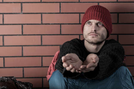 hard times: Young homeless man begging for some money