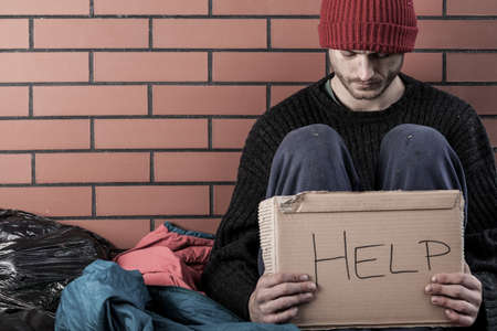 Een dakloze man geld nodig en vraagt om hulp