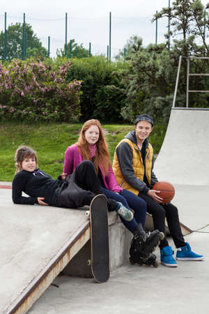 Young friends hanging out at a skate park photo