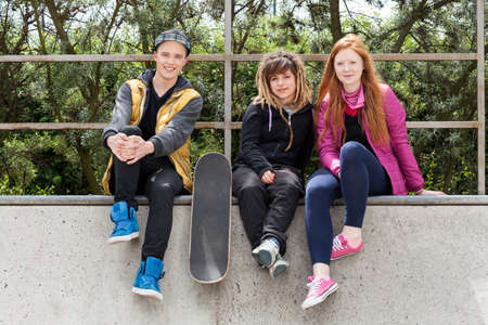 Young friends sitting on a halfpipe in a skatepark photo