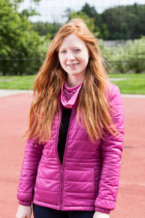 Outdoors portrait of a young redhead girl in pink jacket
