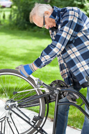 repaired: Older man in glasses repaired pedals a bicycle Stock Photo