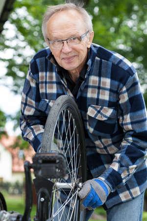 Smiling senior man repairing a bicycle wheel photo
