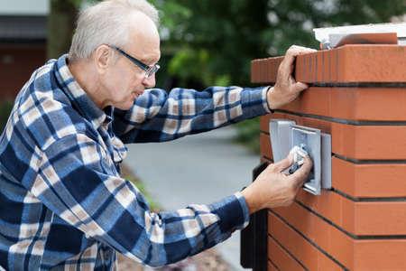 Older man repairing intercom at the gate Stock Photo
