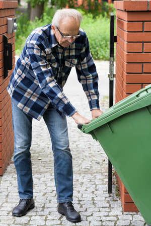 rubbish bin: Senior man is pulling wheeled Stock Photo