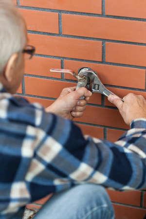 garden key: Elderly man screwed key tap outside Stock Photo