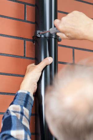 screwed: An older man with a screwdriver screwed gutter Stock Photo