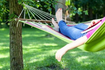책 여름에 그물 침대에서 휴식 젊은 아가씨