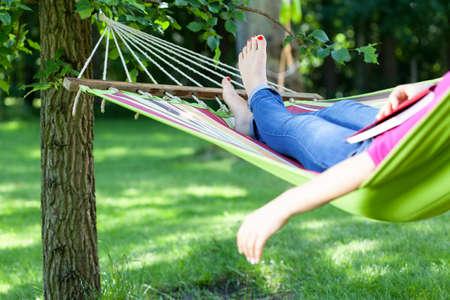 Junge Dame ruht auf der Hängematte mit Buch Sommer Standard-Bild