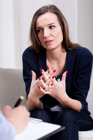 Depressed woman talking about her problems with therapist photo