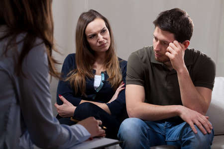 wife and husband: Unhappy at odds couple sitting on psychotherapy session Stock Photo