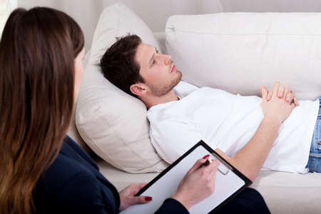 Young therapist working with patient on hypnosis Stock Photo