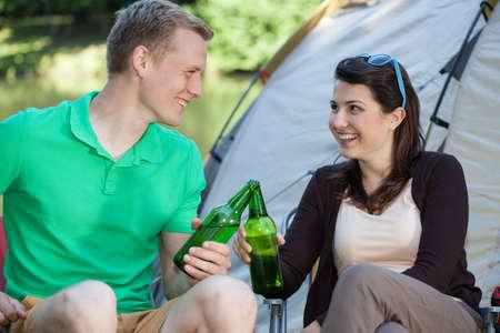 hombre tomando cerveza: La mujer y el hombre bebiendo cerveza en acampar