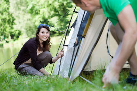 camping pitch: Woman and man pitching a tent together