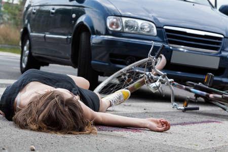 Onbewuste vrouwelijke fietser liggend op straat na verkeersongeval Stockfoto