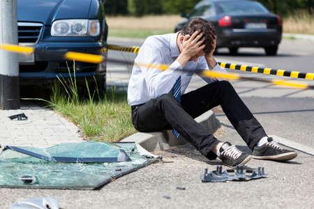 Sad man at road accident scene, horizontal