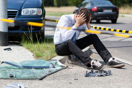 Sad man at road accident scene, horizontal