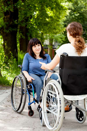 disability insurance: Disabled girls on wheelchairs during talking, vertical