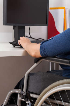 everyday jobs: Disabled woman working next to computer, vertical Stock Photo