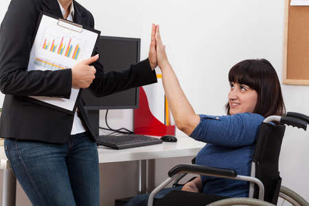 Woman on a wheelchair and her co-worker