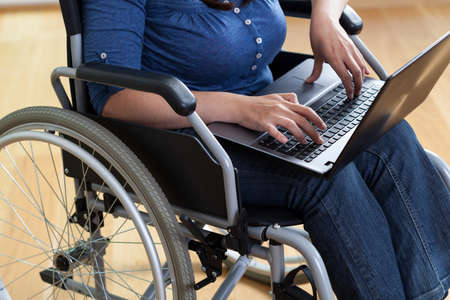 everyday jobs: Woman on a wheelchair with laptop, horizontal Stock Photo