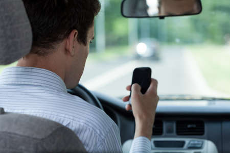 Male driver using mobile phone in car, horizontal photo