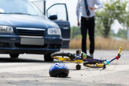 crash helmet: Close-up of a childrens bike and helmet after road accident Stock Photo