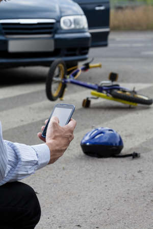 Close-up of a man using his mobile phone to call for help on road photo
