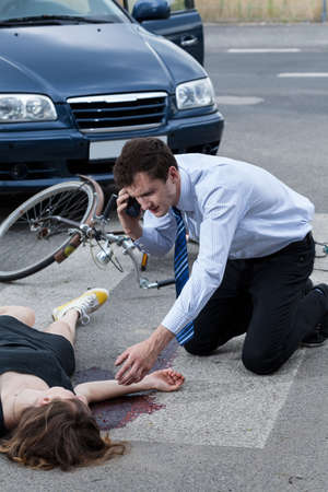 unconscious: Man calling an ambulance for injured woman after road accident