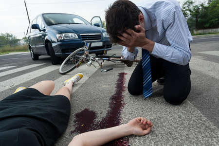 Crying driver and injured woman at road accident scene, horizontal